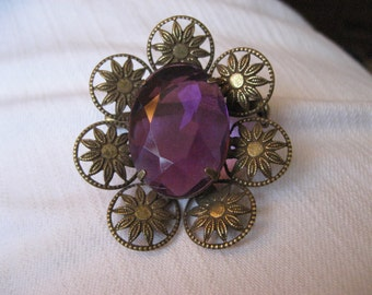 Vintage amethyst colored brooch.  Brass with faceted stone. Filigree.