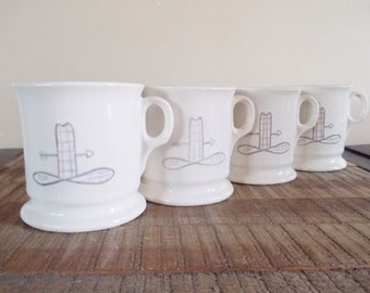 Four Whimsical White Mugs with Simple Cowboy Hat and Arrow Graphic