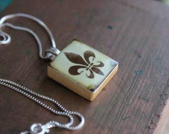 Scrabble Tile Pendant Necklace features a FLOR DE LIS