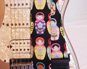 Matryoshka Russian nesting dolls on black guitar strap