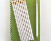 white pencils with gold foil arrow