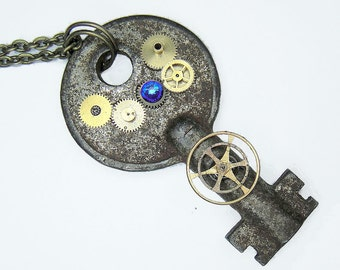 Post Apocalyptic Key Necklace - comprised of gold bronze and brass gears with a deep blue crystal rhinestone