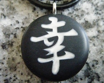 HAPPINESS Japanese kanji symbol hand carved on a polymer clay black color clay background. Pendant comes with a FREE necklace