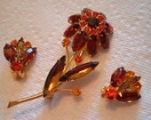 Vintage brooch and clip on earrings.   Amber, orange and gold colored glass stones