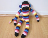 Southwestern stripe sock monkey doll with black, red, pink, orange, and blue stripes