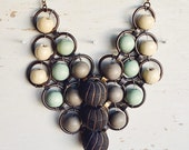 The Tanis necklace, large carved african trade wood beads, grey, mint, and cream beads woven in a antiqued brass bib
