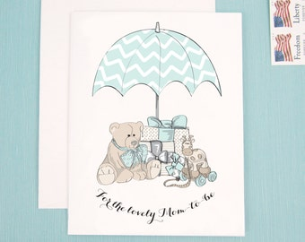 Baby Shower Card, Congratulate Mom to be with adorable illustration of neutral presents, baby toys, and a chevron umbrella