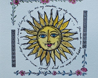 You Are My Sunshine is a cheerful hand pulled artwork of letterpress showing a hand colored sunshine with a flowered border.