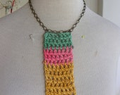 Girl green, pink and mustard colorblocking crochet pendant (bamboo yarn) on golden bronze chain