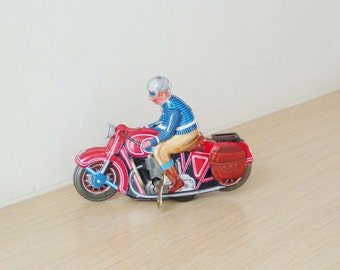 Vintage, wind up biker toy, retro collectible toy of a vintage, red motorcycle, with rider in blue jacket and grey helmet