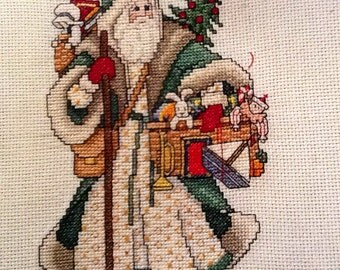 Counted cross stitch Santa in green suit.