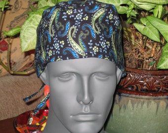 Paisley Scrub cap with black background, bright turquosie, pale green and pale blue details.