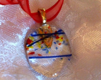 Clear dichroic glass pendant, fused with layers of color.