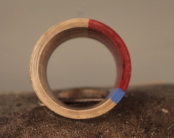 Red/blue/wooden bracelet with a small black heart.