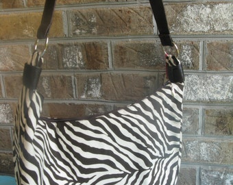 Chocolate brown zebra print with faux leather strap.
