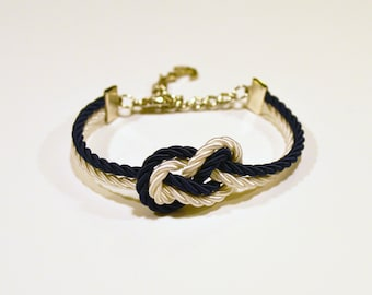 Adjustable navy blue and ivory cream infinity knot nautical rope bracelet with silver anchor charm