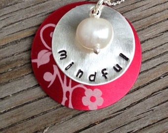 Hand stamped 3/4 inch sterling silver charm on a 1-inch red aluminum frame and 8mm pearl drop- mindful
