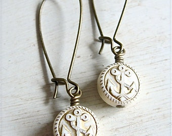 Long style antique brass ivory and gold anchor earrings.