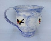 Cute coffee, tea, mug in hues of sky blue, featuring black, yellow and red birds,