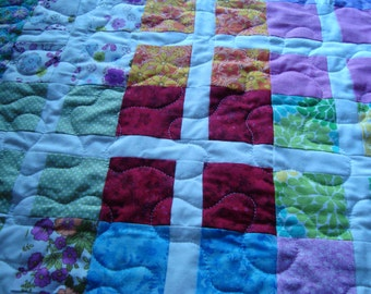 "Infant quilt done in squares of various bright colors trimmed with a white sash. Outlined with a 3"" border of flowers."