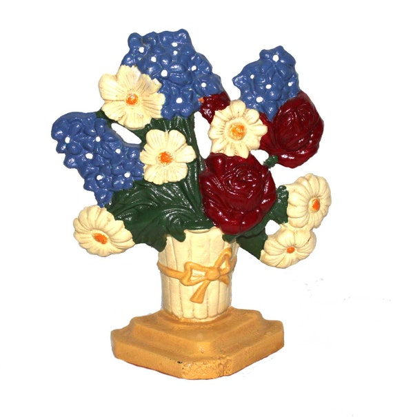 Caste iron doorstop or bookends, cream basket of roses, daisies, and hyacinths on a golden yellow base