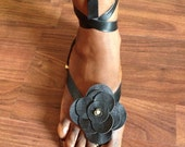 Leather black sandals with a flower on top and ankel straps. Gladiator style.
