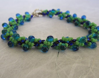 Blue and green spiral rope bracelet with blue drop bumps and a silver plated toggle clasp