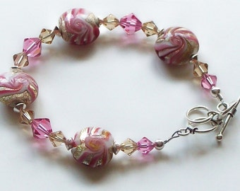 Raspberry colored lampwork and Swarovski crystal bracelet with sterling silver toggle.