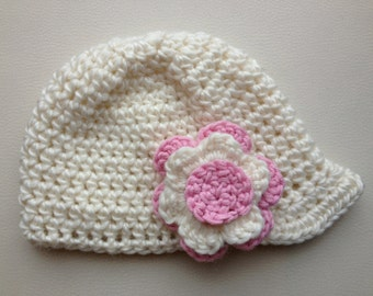 Girls crochet newsboy cap with small peak and flower detail. Off-white cap with dusty pink and off-white flower. Other colours available.