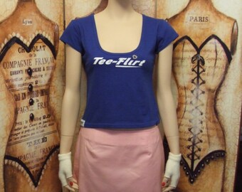 Size medium, scoop neck, cap sleeve fitted tee shirt with Tee-Flirt logo on front