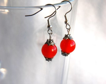 Small earrings, juicy orange glass beads and a metal ornamental bead at the top and bottom.