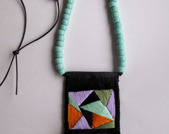 Geometric textile necklace with pendant in mint green purple orange on black leather cord