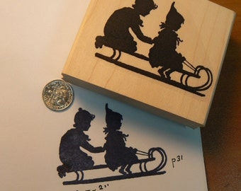 Boy and girl on sled silhouette style rubber stamp WM P31