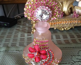Pink perfume bottle with red flower