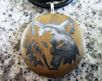 Tribal wolf face hand carved on a polymer clay dark gold color background.  Pendant comes with a FREE Necklace