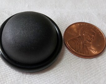 Four black vintage buttons. 1x1 ins and 3x3/4 ins. Dome is 1/4 ins high plus ridge. HMFR13.6-19.37