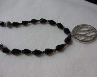 Black bead necklace with silver pendant