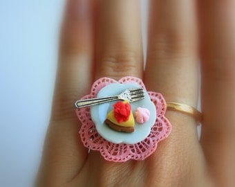 Cheesecake saucer ring - miniature food funny ring with cheesecake, fork and a meringue on a real ceramic saucer.