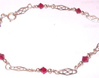 Gold filled bracelet with garnet colored Swarovsky crystals