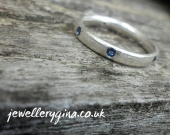 Frosted silver sapphire set eternity ring. Eternity band in frosted silver with sapphires.
