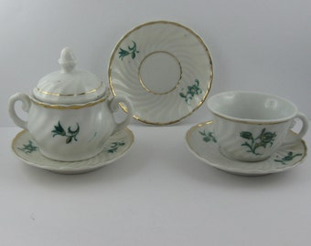 Parts of a porcelain service dishes for dolls: 1 sugar bowl, 1 cup, 3 saucer in white porcelain with flowers and gold rim. Vintage