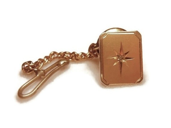 1960s gold plate atomic star burst engraved tie tack with diamond chip.