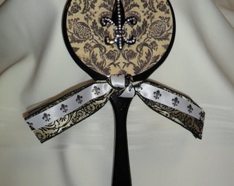 Handcrafted wooden hand mirror. Black base with damask print and fleur de lis embellishment.