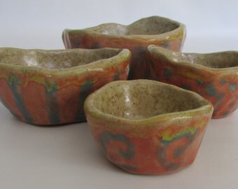 Hand built  set of four small glazed clay bowls