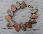 Earthy hand formed stoneware leaves on antique brass bracelet // by Lyn Carey of Earth and Wears