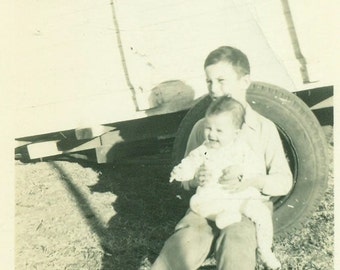 Older Brother Sitting in Spare Tire Holding Baby Sister on Lap Black And White Vintage Photo Photograph