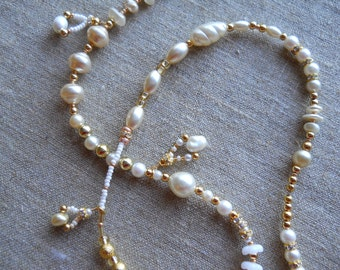White,ivory,and gold  hand strung long necklace, with pearls and asst specialty beads, Handmade dangles add interest and fun. Lovely gift.
