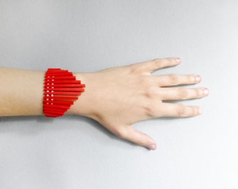 tribal geometric bracelet with red sticks and white beads , contemporary jewelry