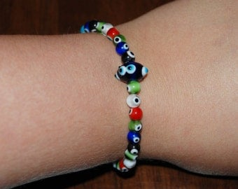 Handmade stretch bracelet in glass multi color google eye beads with large blue accent bead