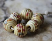 ribbed lampwork bead set pale yellow with rose green and brown speckles